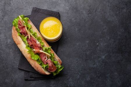 Photo pour Fresh submarine sandwich with prosciutto ham, cheese and lettuce on dark stone background. Top view with copy space for your text - image libre de droit
