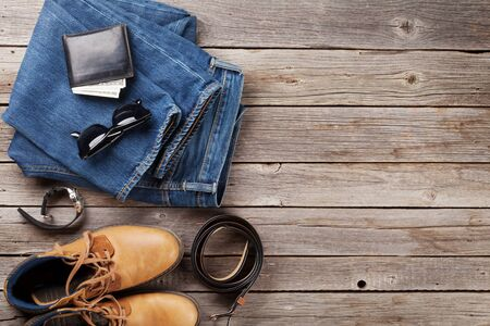 Photo pour Men's clothes and accessories. Jeans, shoes, glasses and wallet with cash on wooden background. Top view with copy space - image libre de droit