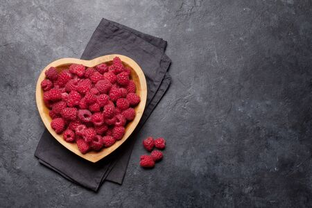 Photo pour Fresh ripe garden raspberry in heart shaped bowl on stone table. Top view with copy space - image libre de droit