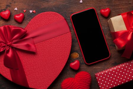 Valentine\'s day greeting card with heart gift boxes and smartphone on wooden background. Top view with space for your greetings or smart phone app. Flat lay