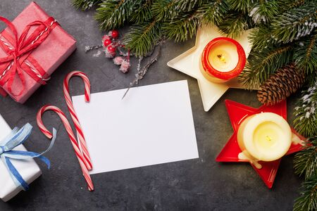 Photo pour Christmas greeting card with fir tree, gift boxes and candles on stone background. - image libre de droit