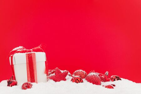 Photo for Christmas greeting card with decor and gift box in snow over red background and copy space for your xmas greetings - Royalty Free Image