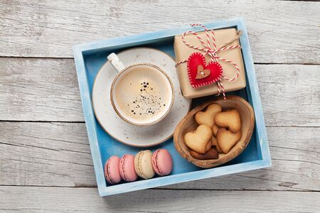 Photo pour Valentines day greeting box with coffee cup, macaroons and gingerbread cookies over wooden background. Top view flat lay - image libre de droit