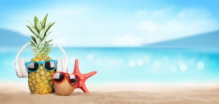 Photo for Summer tropical sea with sparkling waves, pineapple and coconut with sunglasses and headphones on hot sand beach. Travel and vacation concept with copy space - Royalty Free Image