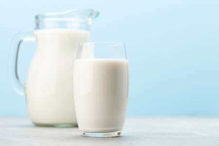 Photo for Milk in glass and jug in front of blue background with copy space - Royalty Free Image