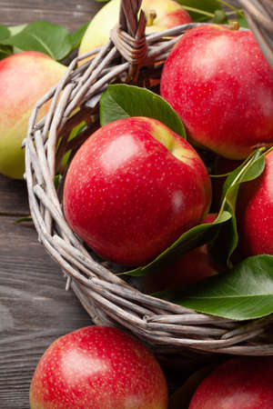 Photo for Ripe garden apple fruits in basket on wooden table - Royalty Free Image