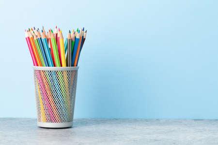 Foto de Colorful pencils. Office supplies or school items in front of blue wall with copy space for your text - Imagen libre de derechos