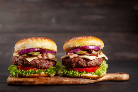 Photo pour Homemade tasty burgers with big beef, cheese, tomato, bacon and lettuce. With copy space - image libre de droit