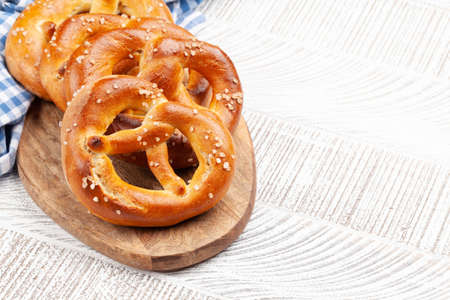 Photo pour Fresh baked homemade pretzel with sea salt on wooden table. Classic beer snack. With copy space - image libre de droit