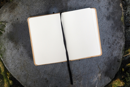 opened empty notebook with black bookmark on gray stone, close up