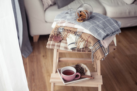 Foto de Plaids. A cup of hot tea. Autumn cozy interior. On a wooden chair is a stack of warm blankets. Candles, leaves, cones, basket, cinnamon. Book and glasses. Autumn. - Imagen libre de derechos