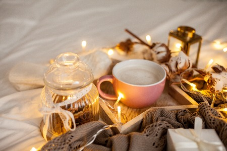 Photo pour Mug of hot cappuccino on a wooden tray is on the bed. Cozy decor. Breakfast. Mug, plaid, cotton, candle. Gift box and knitted mittens. Christmas lights. Holidays. Christmas. Autumn. Winter. - image libre de droit
