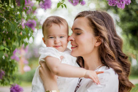 Photo pour Beautiful young mother and little cute daughter are happy near the lilac. Portrait of mom and daughter. - image libre de droit