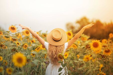 Beautiful curly young woman in a sunflower field holding a wicker hat. Portrait of a young woman in the sun.