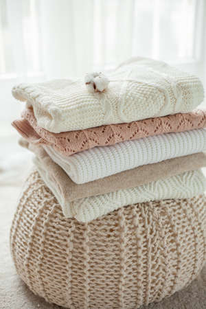 Photo pour A stack of knitted sweaters, cotton. Women's sweaters lie on the ottoman. Cozy autumn clothes. Fall. - image libre de droit