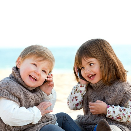 Portrait of two cute little girls o beach talking on mobile phones