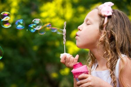 Close up portrait of cute little girl blowing bubbles in garden
