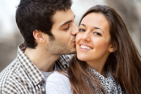Close up portrait of boy kissing girlfriend on cheek outdoors