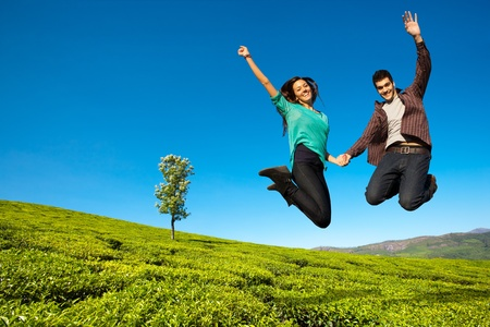 Photo pour Happy couple jumping with hands raised in green field  - image libre de droit