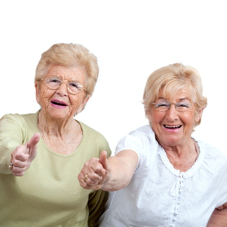 Photo for Close up portrait of two friendly senior women showing thumbs up Isolated on white  - Royalty Free Image