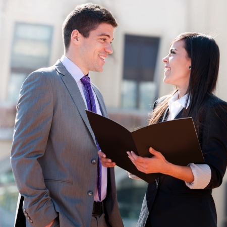 Close up of young business couple with file outdoors.