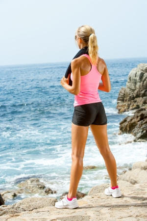 Young attractive woman looking at sea after fitness workout.