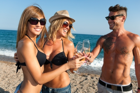 Happy young group of friends making a champagne toast on beach