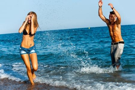 Young couple having great time splashing water at seashore