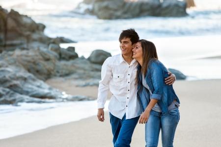 Cute happy teen couple wandering along the beach.