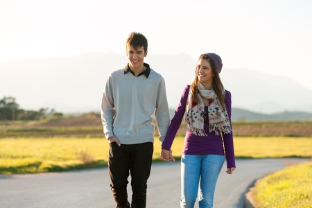 Young couple wandering along road in countryside.
