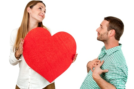 Close up portrait of couple playing around with big red heart symbol.Isolated on white background.