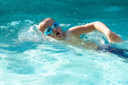 Photo pour Small boy practicing in open air swimming pool. - image libre de droit