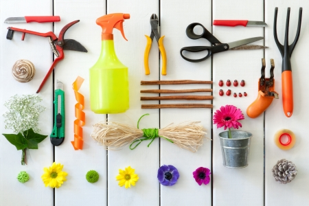 Close up of gardening and florist tools on white wooden background.