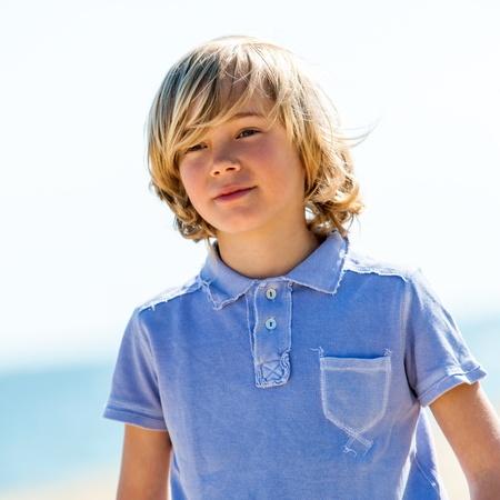 Portrait of cute boy wearing blue polo shirt outdoors.