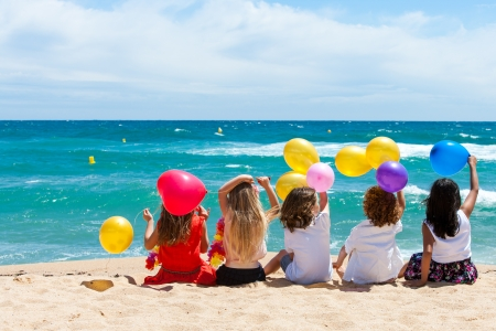 Young kids holding color balloons sitting on beach.