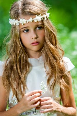 Close up portrait of cute girl in white dress holding flower outdoors.