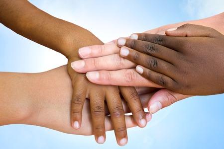 Foto de Close up of multiethnic children's hands making pile against blue sky. - Imagen libre de derechos