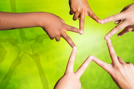 Multiracial children's fingers touching to make star shape.