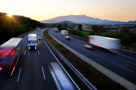 Colorful Twilight scene of frenetic highway with fast moving vehicles in blurry motion.