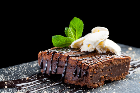 Photo pour Macro close up of appetizing chocolate brownie with dark chocolate dressing and vanilla ice cream against black background. - image libre de droit
