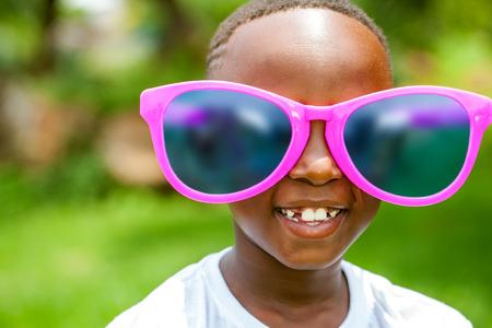 Photo pour Close up face shot portrait of cute African boy wearing huge over sized sun glasses outdoors. - image libre de droit
