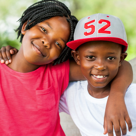Photo for Close up face shot of smiling African boy and girl outdoors. - Royalty Free Image