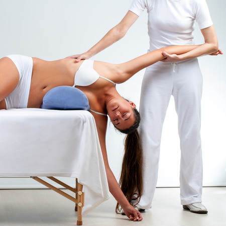 Osteopath stretching woman's shoulder on massage bed at session.