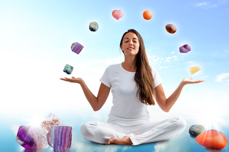 Full length portrait of young woman dressed in white doing yoga with precious gemstones.Conceptual dream scape with colorful gemstones floating around girl.