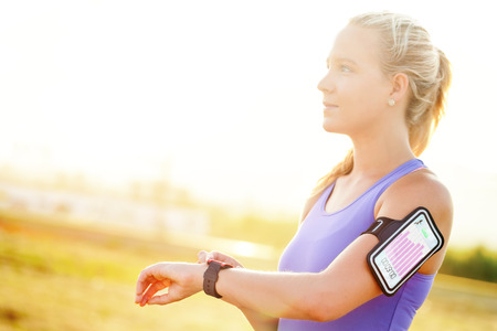 Photo pour Close up portrait of attractive young woman setting workout on smart watch.Girl in sport wear with fitness chart showing on smart watch. - image libre de droit