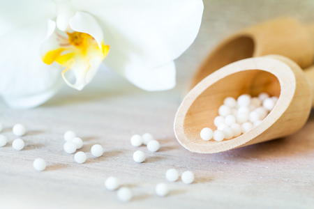 Macro close up of homeopathic balls with orchid.