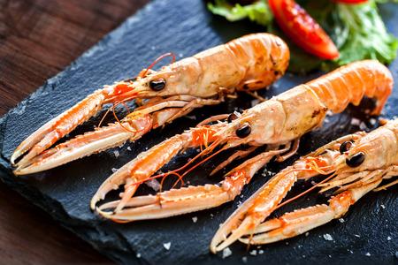 Macro close up of fresh grilled crawfish platter with green salad served on elegant black tile.