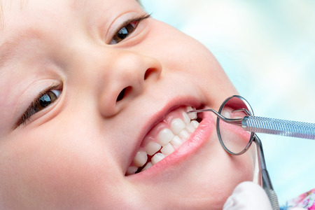 Photo pour Macro close up of little life year old showing teeth at dental check up.Dentist hands holding mouth mirror and hatchet near teeth. - image libre de droit