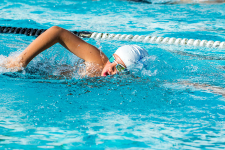 Close up action shot of Teen boy swimming freestyle at swimming lesson.