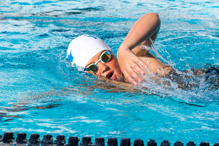 Close up action shot of teen student doing freestyle at swimming lesson.